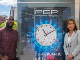 Victoria Frye (right) and Jeremy Fagan (left) in front of PEPTALK ad on 132nd street and Adam Clayton Powell Jr. Boulevard.