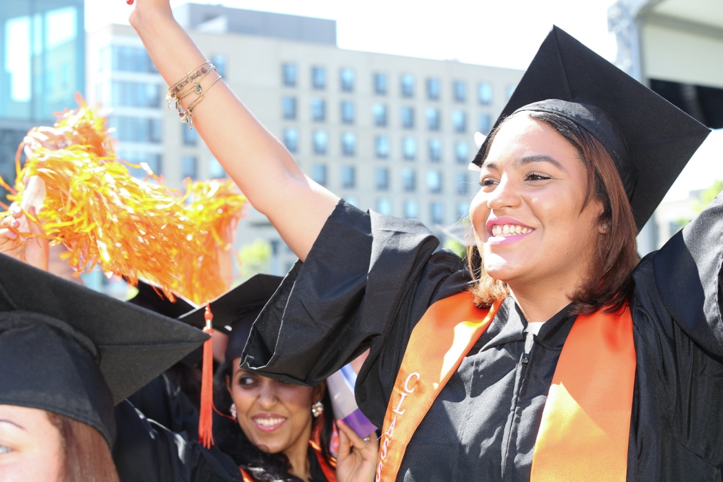 Photo of young women at commencement waving pom poms