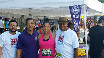 Sarai Perez (second from the right) and fellow runners at the CCNY information booth before the 5K run.
