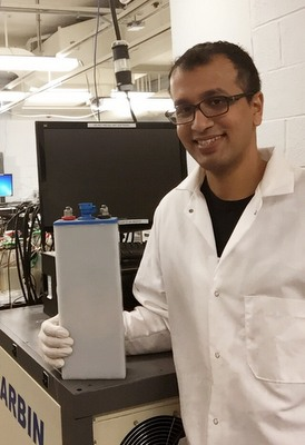 Gautam Yadav with the low cost, rechargeable high energy density battery developed at CCNY's Grove School of Engineering.