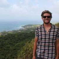Dr. Matthew Reilly stands on the top of a mountain with the view of a mountain and beach coast behind him. He is smiling, wearing sunglasses.