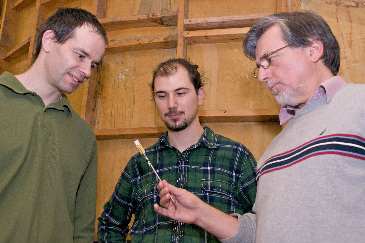 Professor Niell Elvin (left), graduate student Dogus Akaydin and Professor Yiannis Andreopoulos discuss properties of a piezoelectric strip (in Professor Andreopoulos' hand) that generates electricity when an air flow passes over it.