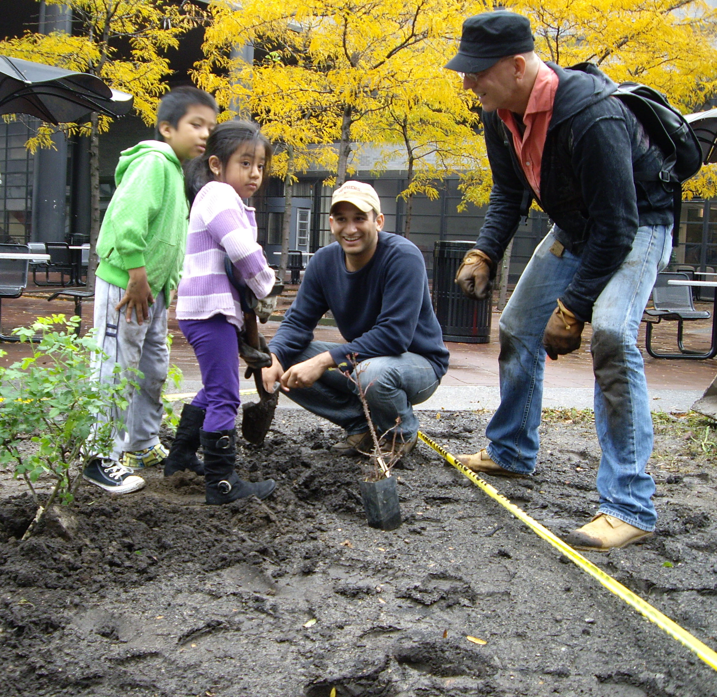 Two young residents help Paimaan Lodhi [middle], Urban Planner in the Office of the Manhattan Borough President, and Dane Twining of the Heritage Rose Foundation at the heritage rose planting at CCNY.