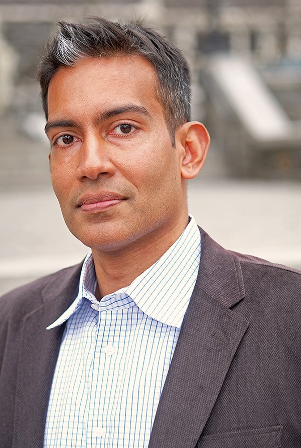 Dr. Stanley Thangaraj, wearing a blue and white striped button-down shirt and a grey blazer, looks into the camera. A section of CCNY's campus is blurred in the background.