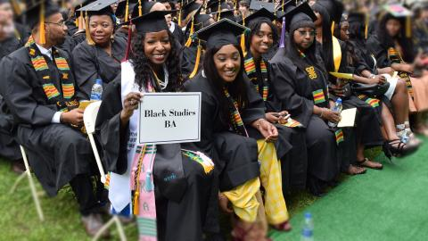 "Students at the 2018 Graduation- they are all in cap and gown- about 30 people are int he photo but 5 are looking into the camera- they are holding a sign that reads "" Black Studies BA"""