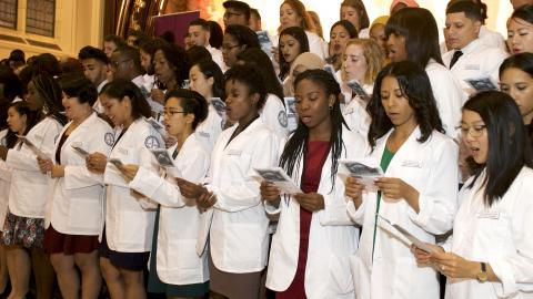 students wearing white coats at a ceremony in the great hall of shepard hall