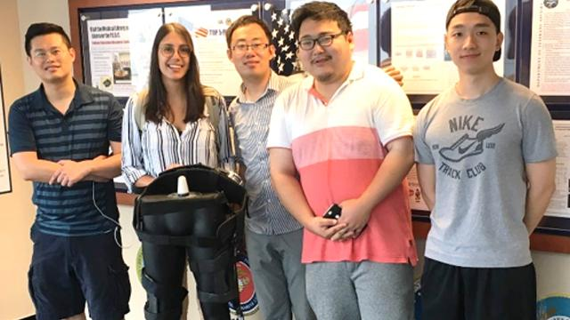 CCNY Mechanical Engineering Professor Hao Su [third from left] with members of his research team and a model of their exoskeleton.
