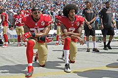 football players taking a knee at a game